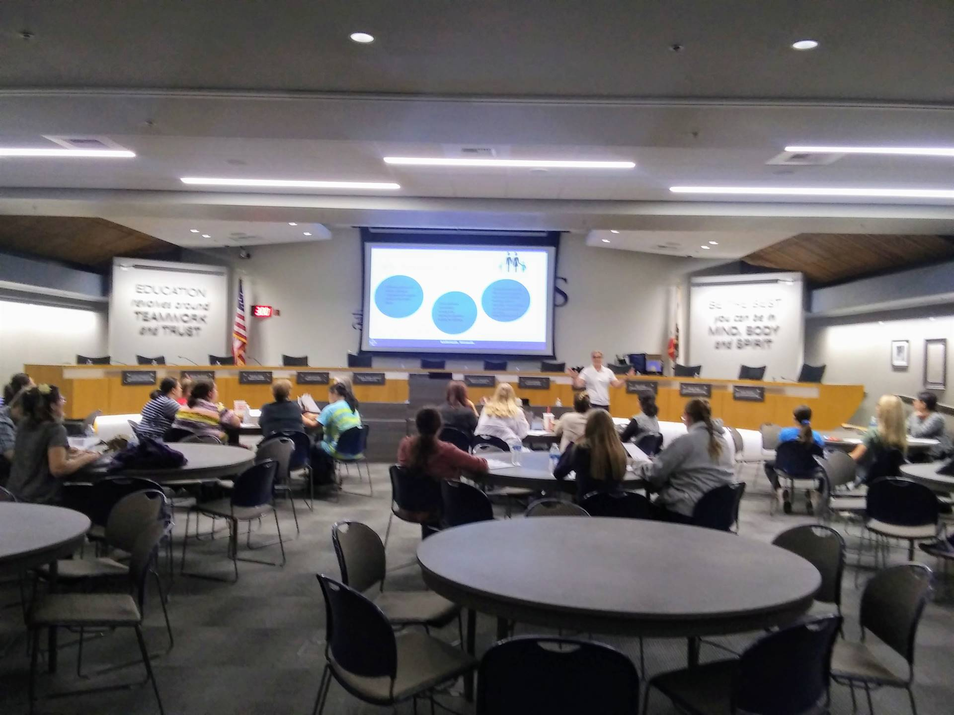 FRC workshop at CUSD boardroom gray round tables, projection screen and many people
