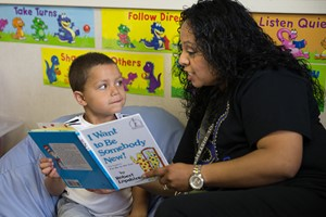 Teacher reading book to student